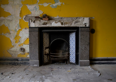 Broken fireplace in yellow bedroom